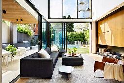 Elegantes Wohnzimmer mit doppelter Raumhöhe, offene Glasschiebetüren zum Garten und zur überdachter Terrasse
