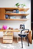 Schreibtisch mit Stuhl, darüber Holzregal im Arbeitszimmer