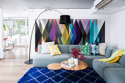Gray upholstered sofa with cushions, coffee table and arc lamp in the living room, colorful wallpaper with a geometric pattern on the wall