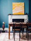 Holztisch mit Stühlen vor Kamin, moderne Kunst in Gelbtönen auf Kaminsims