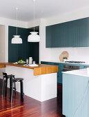 Einbauküche mit blau-grau lackierter Holzfront und Kücheninsel