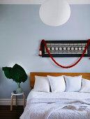 Wandbehang über Doppelbett im Schlafzimmer, Vase mit Blättern auf Hocker
