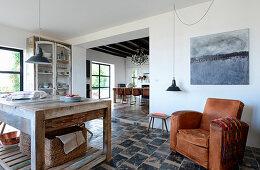 Rustikale Wohnküche mit Natursteinfliesen und Ledersessel