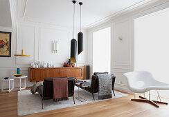 Zwei schwarze Liegen, Pendelleuchte, weißer Klassiker-Liege und Sideboard in weißem Wohnzimmer