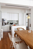 Wooden table and white classic chairs, kitchen counter and white fitted kitchen in open-plan interior