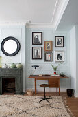 Teak desk next to marble fireplace, gallery of photographs and round mirror on mint-green wall