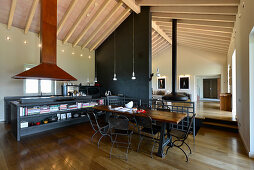 Huge extractor hood in kitchen-dining area and black partition in open-plan interior