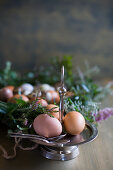 Two boiled eggs and spoons on cake stand