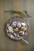Boiled quail eggs and spoon on silver tray