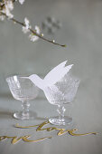 Paper hummingbird in vintage wine glass