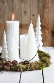 White Christmas candles in handmade wreath of moss and larch twigs