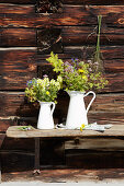 Bunches of wildflowers in white enamel jugs