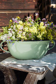 Lady's mantle, cow parsley, flax and cranesbill in green pot with handle