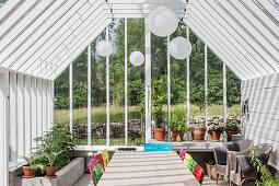 Bunte Stühle am Tisch in einem Glashaus im Garten