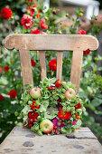 Late-summer wreath of hops, green hydrangeas, zinnias and apples on garden chair