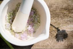 Schnittlauchblütensalz selber machen: Blüten und Salz in einem Mörser zerkleinern