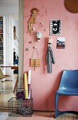 DIY coat rack made from coat hooks and oversized clothes pegs on pink wall