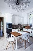 Transparent chairs around table below designer ceiling lamp in kitchen