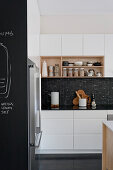 Modern black-and-white kitchen with shelves and chalkboard wall