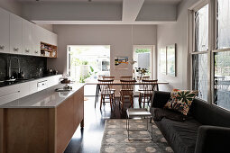 Dark sofa in open-plan kitchen with dining area in front of doors leading to garden