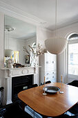 Dining table next to open fireplace in classic period building with stucco ceiling