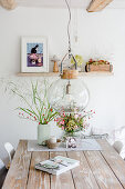 Autumn arrangements with rose hips and book on wooden table below pendant lamp with glass lampshade in rustic dining room
