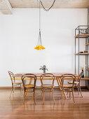 Esstisch mit Bugholzstühlen unter Pendelleuchte mit gelben Schirmchen