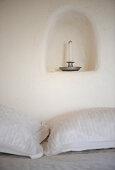 Kerzenhalter mit Kerze in einer kleinen Wandnische überm Bett