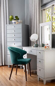 White dressing table and petrol-blue velvet chair next to tallboy