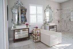 White, rectangular bathtub between twin washstands with opulent mirrors in elegant, luxurious bathroom