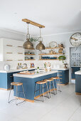 Blue base units and bar stools in modern country-house kitchen