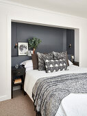 Double bed with head in dark-painted alcove