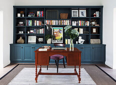 Antique desk in front of bookcase in study