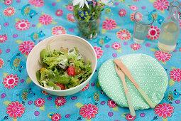 Bowl of salad, handmade oilcloth bowl cover and wooden cutlery