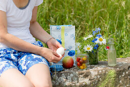 Woman peeling a boiled egg at a picnic