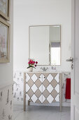 Washstand with diamond patterned front below wall-mounted mirror in bathroom