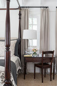 Table lamp on antique table and chair next to four-poster bed in country-house bedroom