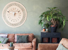 Brown leather sofas and wall hanging with animal skull in living room with green wall