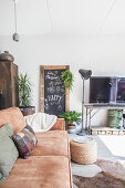 Brown leather sofa, chalkboard, standard lamp and vintage TV stand in living room
