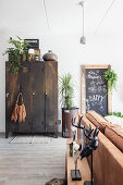 Vintage metal locker, houseplants, chalkboard and brown leather sofa in living room