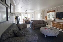 Graue Sofas und runder Korbtisch im Wohnzimmer im Hamptons-Stil