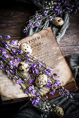 Quail eggs and purple flowering branches between open pages of an old book