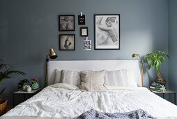 Double bed with white bed linen in bedroom with blue-grey wall