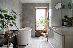 Free-standing bathtub in bathroom with grey floor tiles