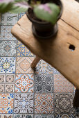 House plant on wooden stool on floor tiles with Oriental patterns