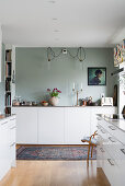 White cupboards in kitchen with pale grey wall