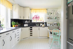 L-shaped kitchen counter in bright kitchen-dining room with white wooden floor