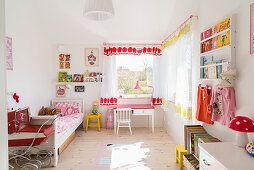 Bed, child's table, chair and shelves in girl's bedroom with pale wooden floor