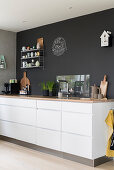 White kitchen counter with drawers and wooden worksurface against charcoal wall
