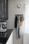 Kitchen utensils hung from row of hooks on pale grey wall next to kitchen counter